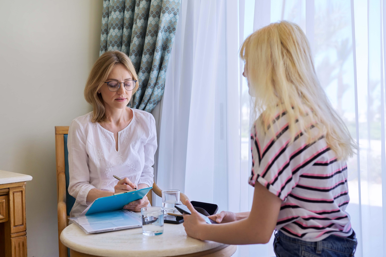 Två kvinnor sitter vid ett bord och den ena antecknar.