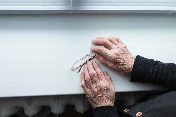 Äldre kvinnas händer håller i ett par glasögon.