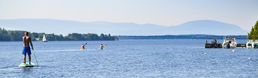 Bild på en hamn, fjällen i bakgrunden, några badar och en paddlar paddelbord. Fotograf:  Göran Strand