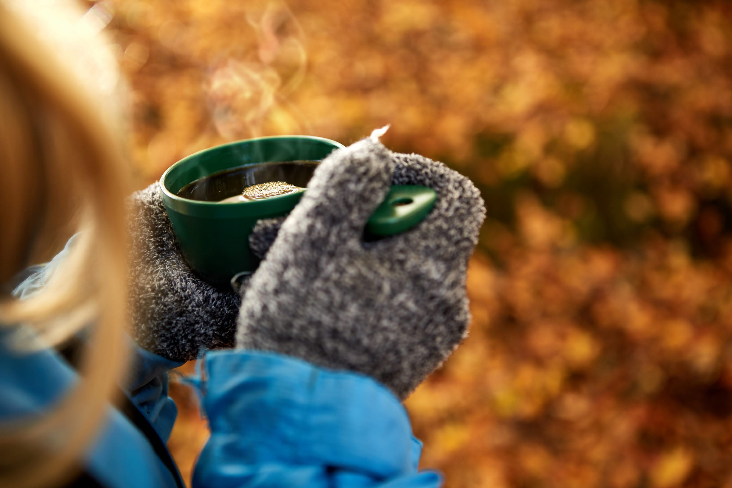 542 Woman wearing mittens holding a smoking hot cup of